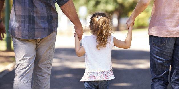 Child holding parents hands.jpeg