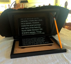 Draped with black, felt cloth, this DIY teleprompter works like a charm!