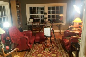 Looking from behind subject chair: fill on left, main light on right, camera and teleprompter in the middle.