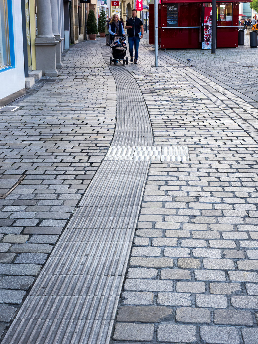 The grooved sidewalk strip is for blind people and where it juts out indicates to them where there is a street crossing light!