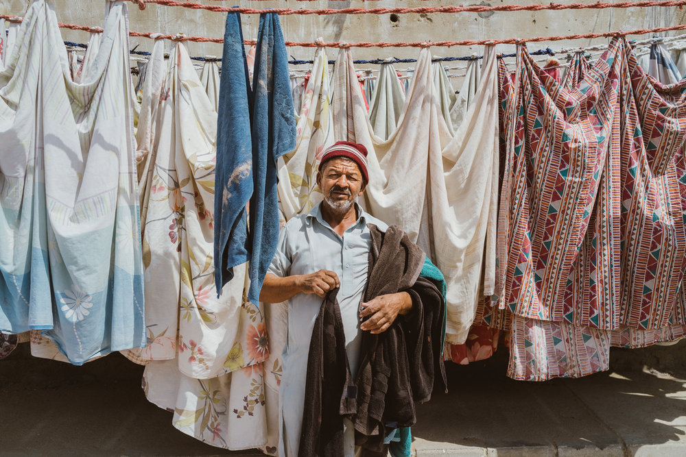 Mr. Faraz, drying clothes next to his laundry service, Karachi, Pakistan.