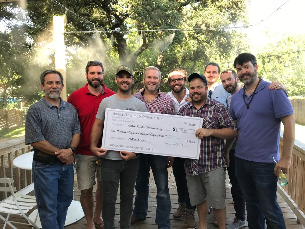 The PHAUS Austin crew delivering fundraiser check to the Austin Habitat For Humanity team.