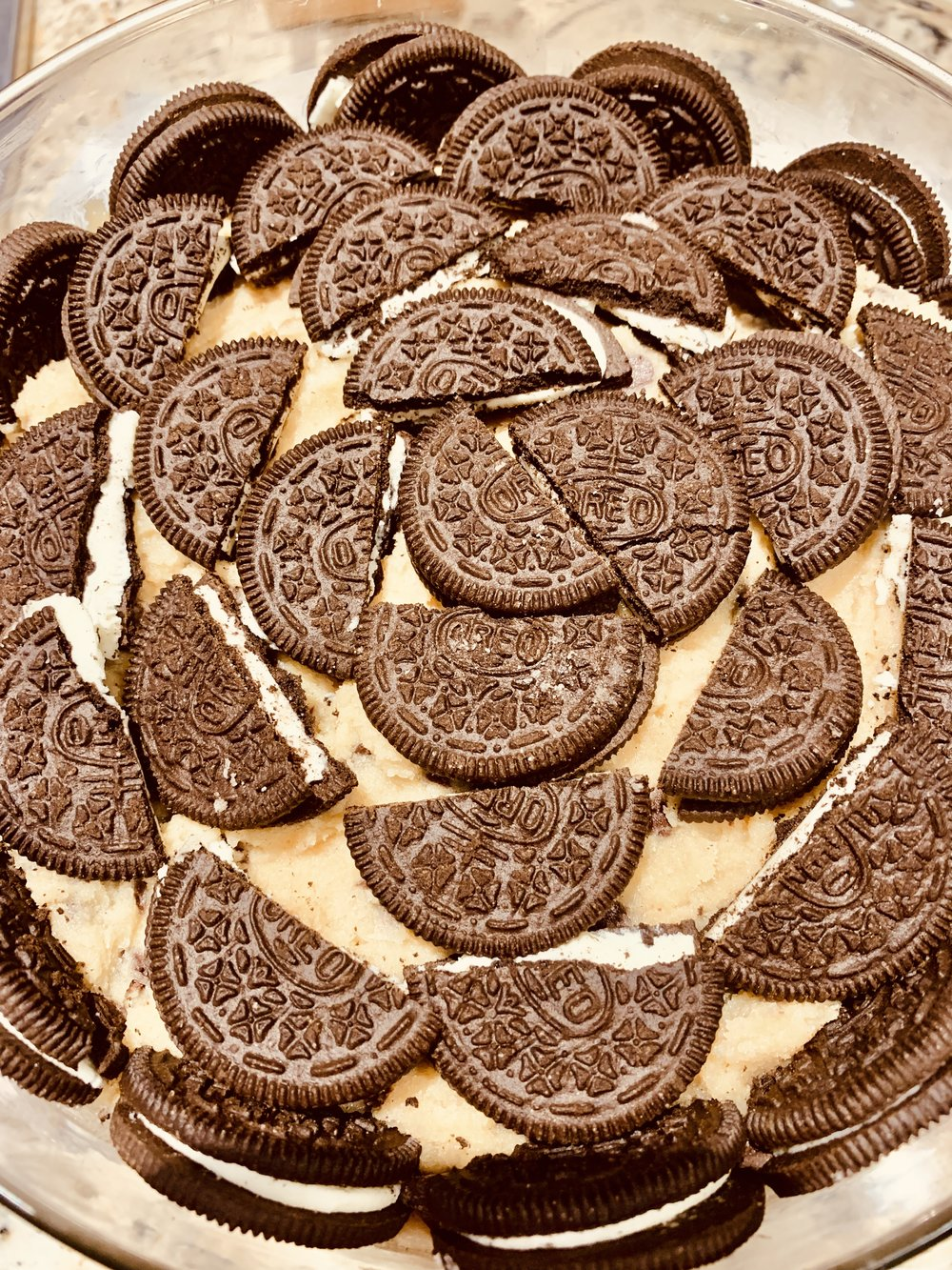 - Add halved Oreos. Pipe the outside with the half-moon shapes and then lay more in the center.