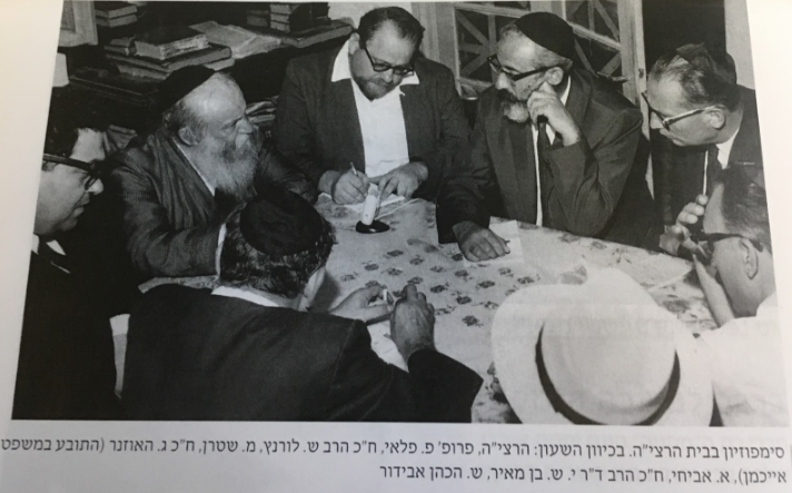 Photo of journalist Pinchas Peli to the left of Rabbi Zevi Yehudah Hakohen Kook, taking notes of the conversation. This symposium took place in the home of Rabbi Kook at 30 Ovadiah Street in the Ge'ulah section of Jerusalem. Peli is seated between Rabbi Kook and MK Rabbi Shlomo Lorincz. Also present during the discussion is Gideon Hausner (who prosecuted Eichmann).