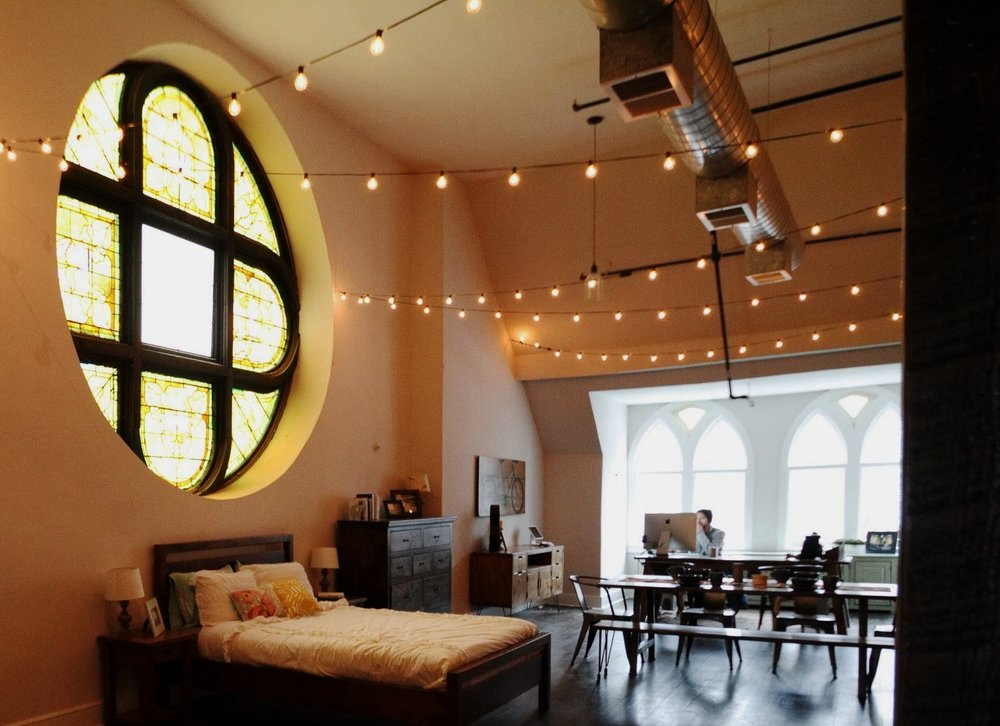 an original stained glass window overlooks a custom Unruh bed