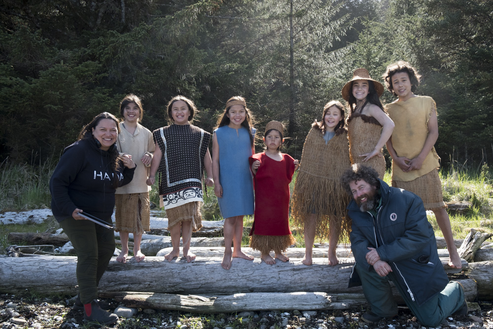 On location in the historic village of Yan, Helen with young cast members and co-director Gwaai Edenshaw (kneeling far right. Photo by Farah Nosh/Niijang Xyaalas