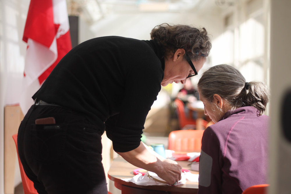 Helene Vosters helps a participant embroider one of the TRC calls to action onto a Canadian flag.