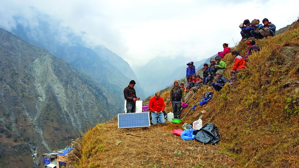 Navin Thapa, left, UTEP Department of Geological Sciences Research Associate Galen Kaip, and Nepalese driver Bijaya Khadka work with seismic sensors as local villagers watch. Photo courtesy of Marianne Karplus