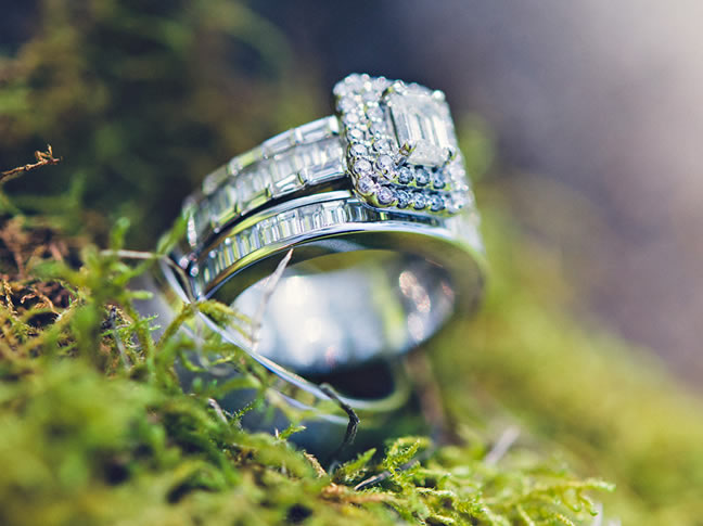 Picture-perfect engagement rings. An emerald cut centre diamond surrounded by two halos and embedded into a diamond band. Two small emeralds glisten underneath the centre stone to commemorate Abaigeal's Irish heritage.