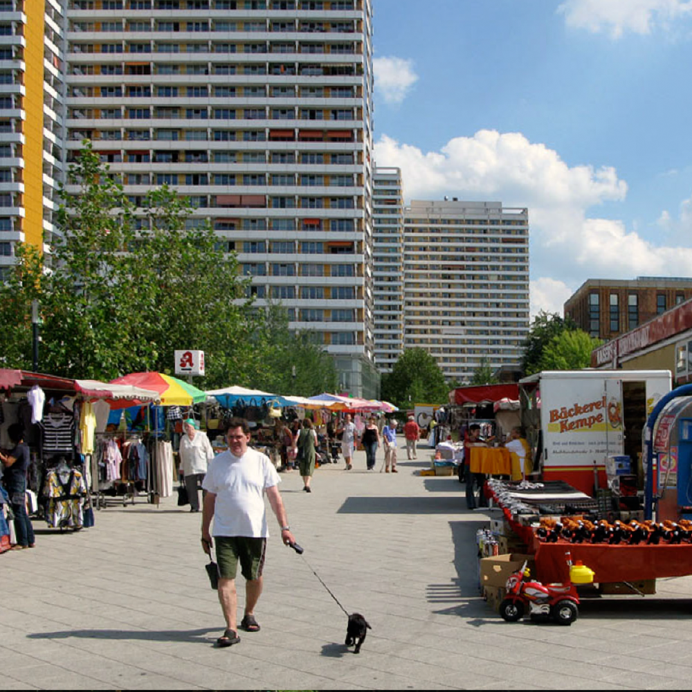 The scale in-between apartment towers feels different when they are activated by weekly markets.   Berlin, Germany