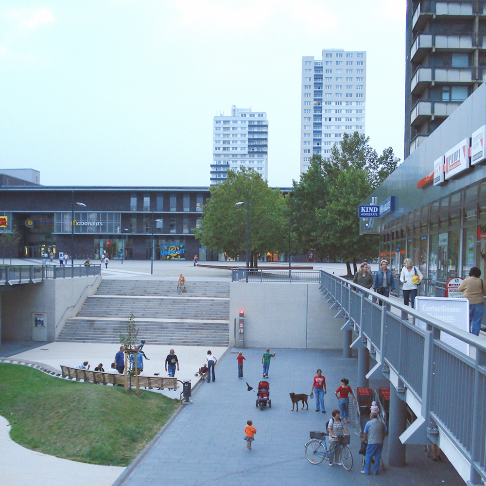 A public square and raised commercial promenade create draws for people to visit a space. Either way, care for the public realm creates spaces for people to gather.   Halle Neustadt, Germany