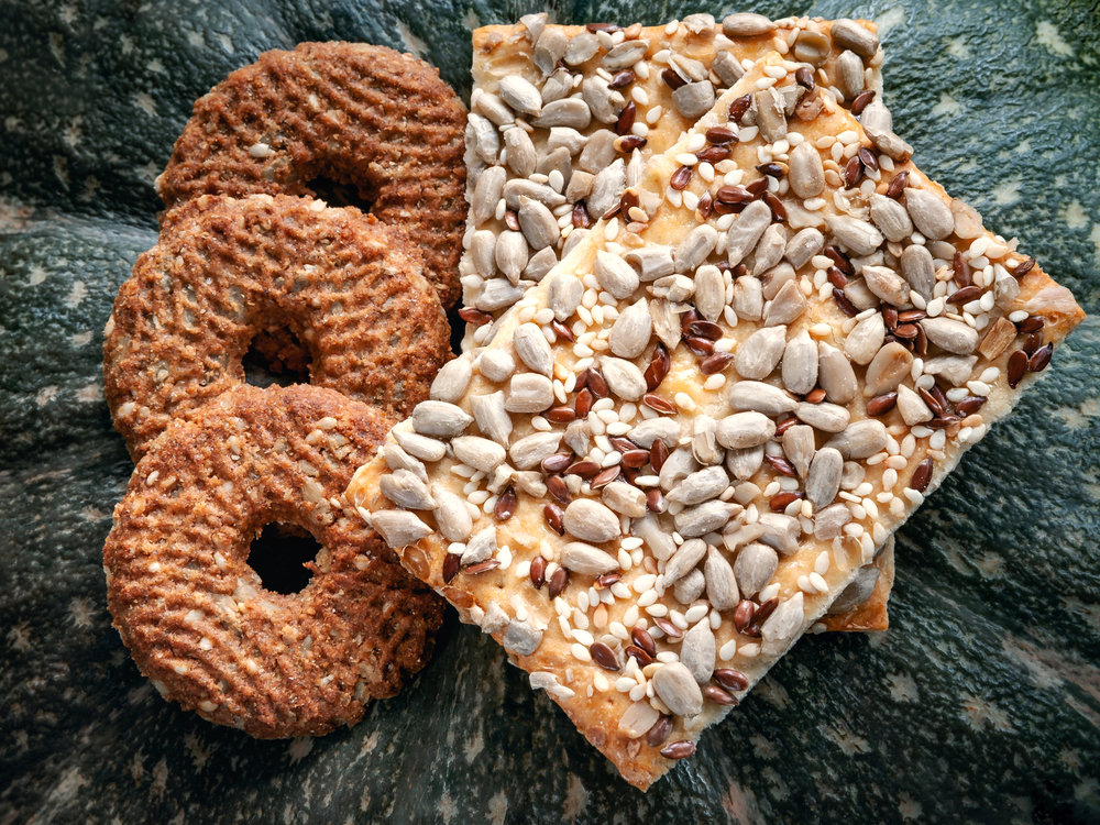 The cracker on the right is a variation of crisp bread with the seeds on top. The cracker above is lighter in color than the cracker recipe below because the recipe calls for buckwheat.