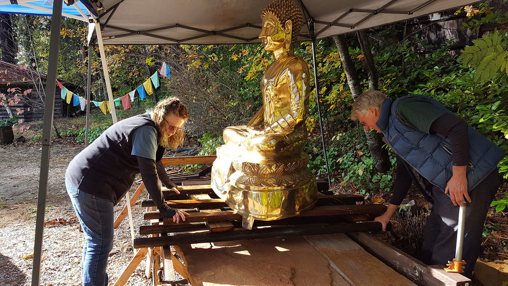 Ann and Rick carefully moving Buddha onto the stone pedestal
