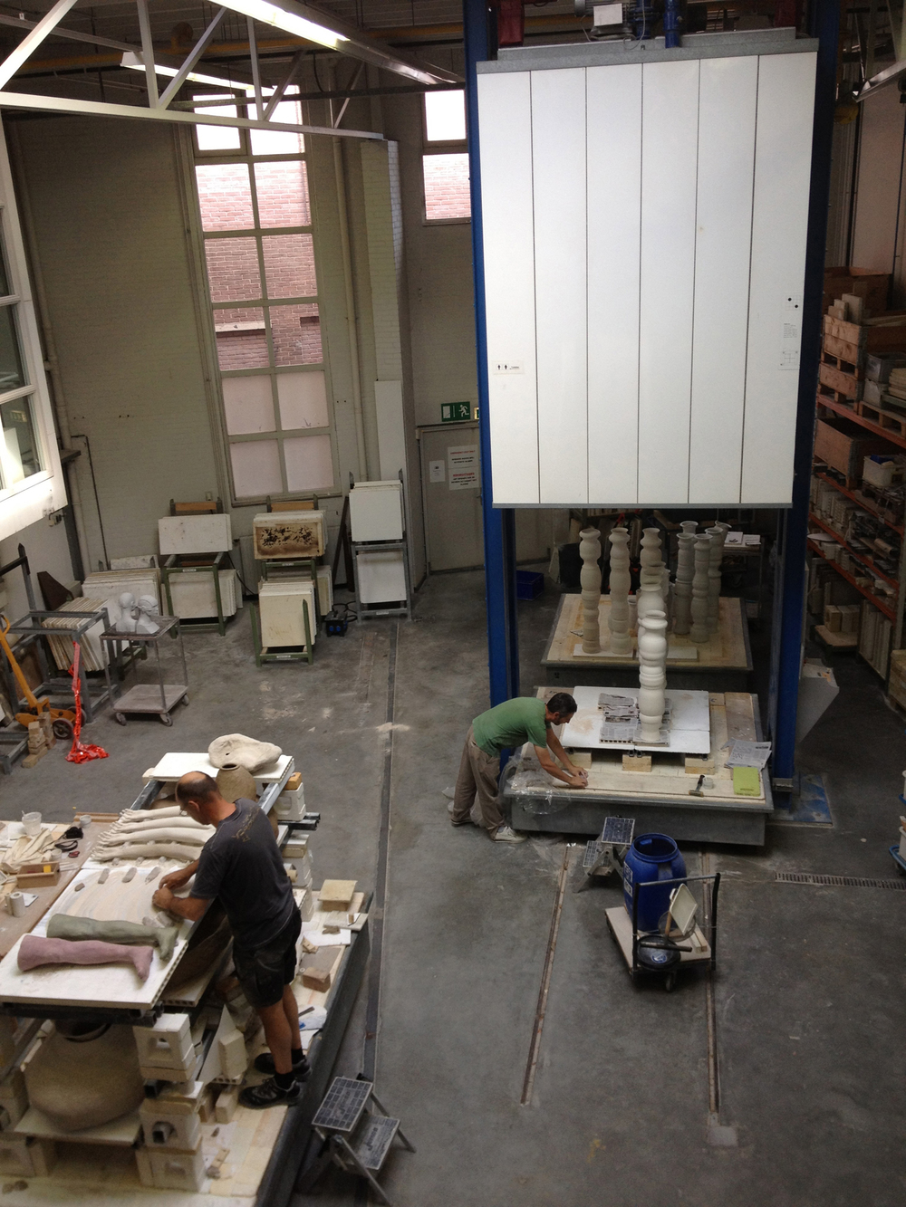 Technical staff at the European Ceramic Work Centre, in its (former) 's-Hertogenbosch premises, load work by artists Simon Bedwell (L) and by Jieun Yoo (R).