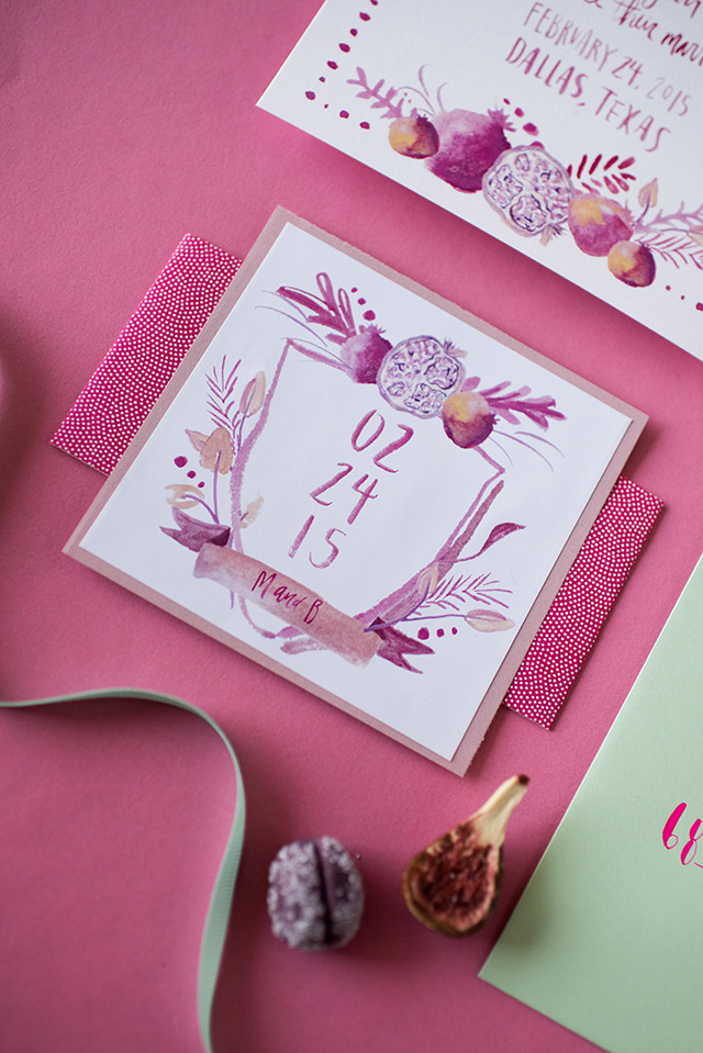 A close-up look at this custom wedding crest for a summer pomegranate themed style. Hot pink and purple hues with pops of mint green.