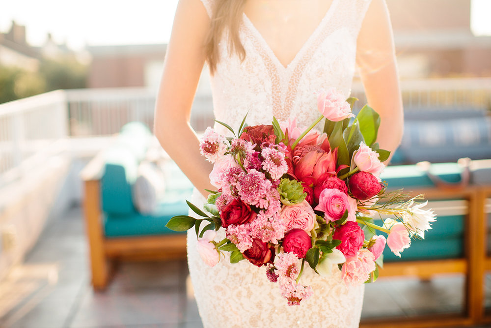 Summer wedding bouquet filled with pinks and deep reds.