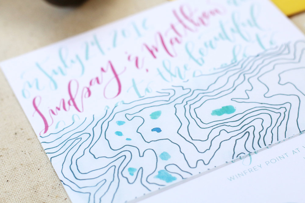 Goldie Design Co. created a custom belly band to wrap around the suite that showed a hand drawn topographic map of the location of their Colorado elopement!