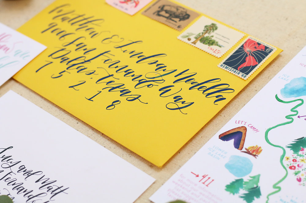 Bright yellow envelope with navy calligraphy and vintage stamps for Colorado elopement wedding invitations