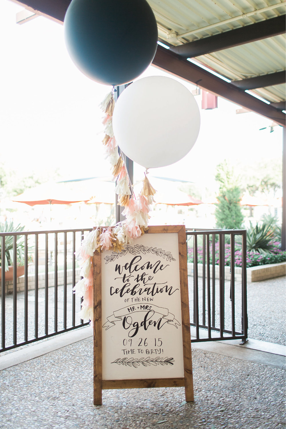 Wedding welcome signage on a handmade wooden easel board, decorated with tassel strings and oversized balloons!