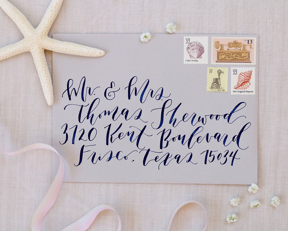Gorgeous outer envelope for formal Cabo wedding with navy blue calligraphy and vintage stamps