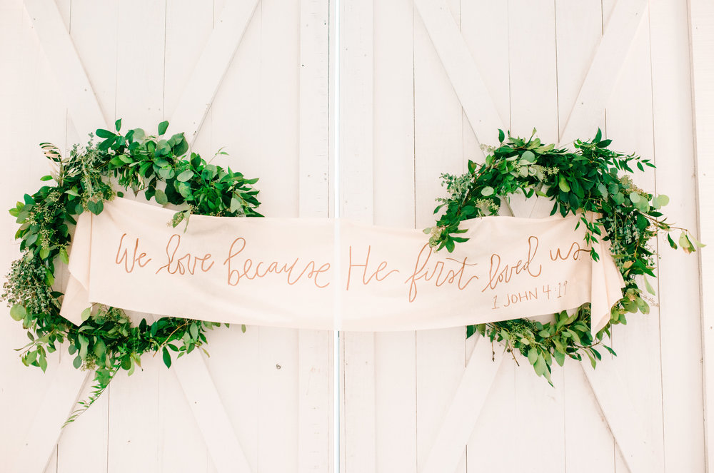 Custom fabric lettered with bible verse hand lettered as a ceremony backdrop at the White Sparrow Barn.