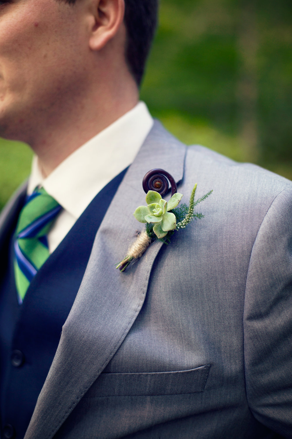 boutonniere with succulents by branches & vine