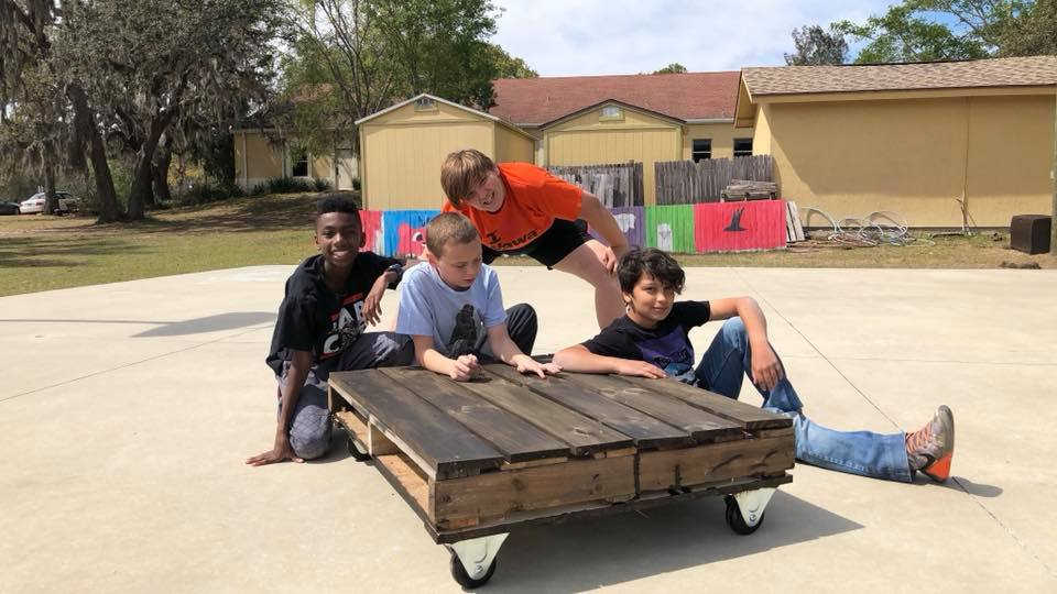 Middle School boys with their completed DIY pallet coffee table!
