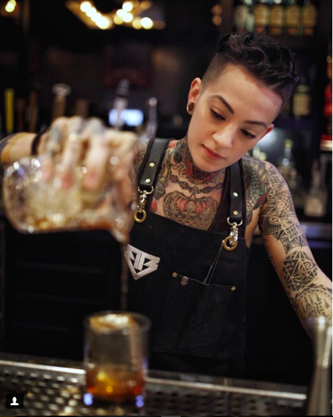 Bad Birdy pouring an old fashioned, sporting a customized apron from Search and Rescue Denim