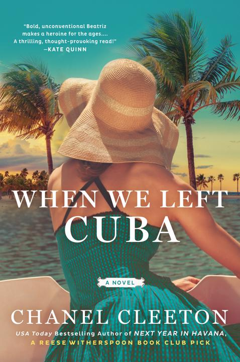 The cover of  When We Left Cuba , featuring a woman in a mid-century dress and sun-hat facing away, toward  the ocean and palms