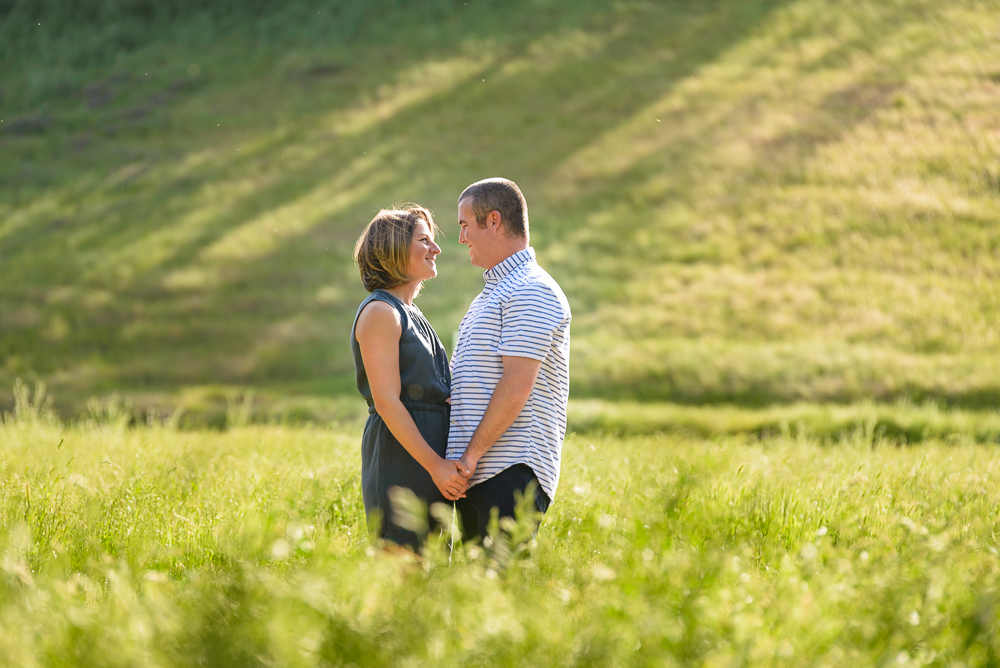 Couple in golden light standing in tall grass