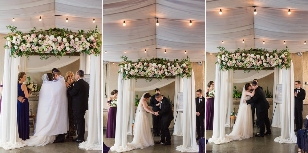 Bride and groom under the chuppah with parents