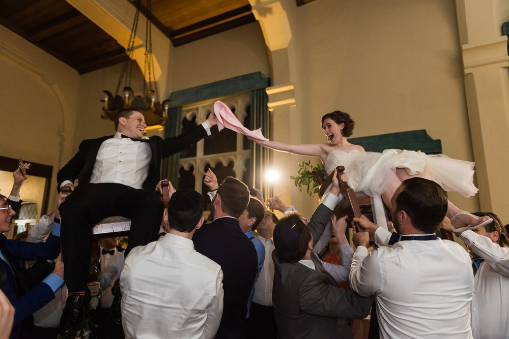 Bride and groom in chairs for the hora dance