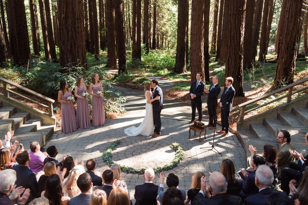 Bride and groom kissing in redwood grove