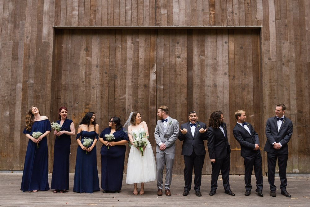Silly wedding party photo in front of wooden wall