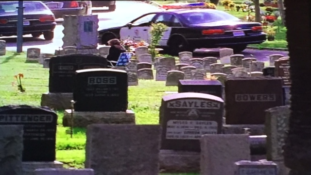 In the cemetery, the cops are leaving. There's a person in a lawn chair, for some reason, and the Sayles grave that places this cemetery in LA instead of SF.