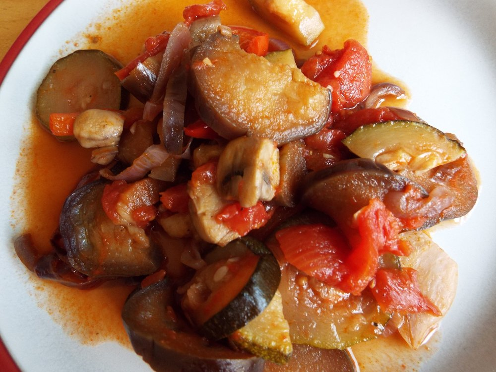 Ratatouille made with aubergine (eggplant), courgettes (zucchini), onions, mushrooms, peppers (capsicums) and tomatoes, with dried herbs and garlic