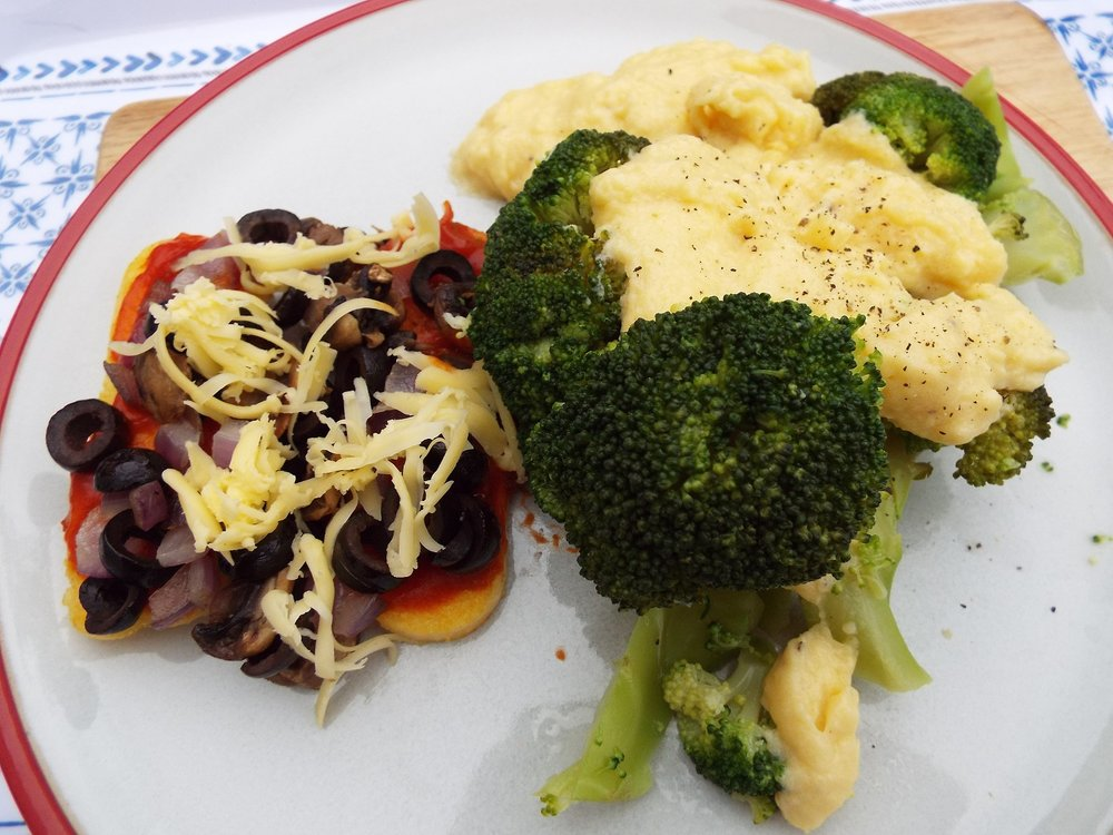 Polenta slices, fried in olive oil, with toppings of tomato, onion, black olives, mushrooms and vegan cheese, with broccoli in cheese sauce