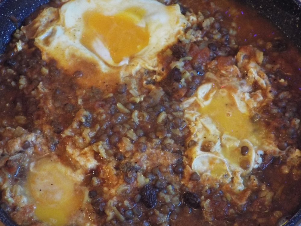 Persian omelette - lentils, rice, onions, tomatoes and raisins, spiced, with eggs cooked on top