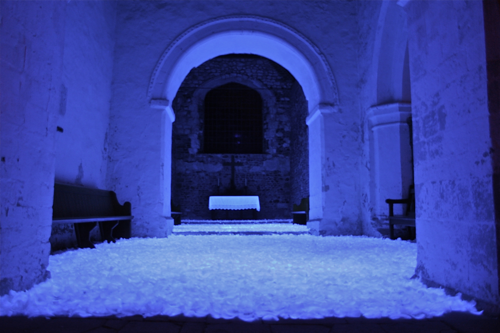 80,000 white feathers are arranged on the empty chancel floor of the Old Saxon Church. Three UV cannons overhead illuminate the piece, making the feathers glow. Ten hidden audio speakers were placed around the site to create an abstract surround sound experience, sourced from sound recordings of the church's own single bell, which was then edited and manipulated. The work could only be viewed from the entrance of the chapel, the feathers barring access to the whole church. Photo Credit: Mat Clark