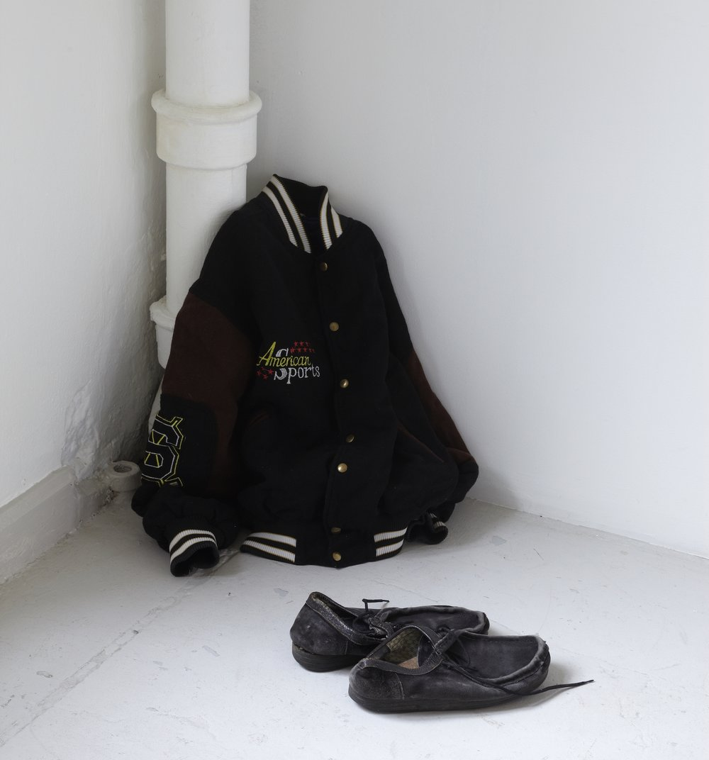 Amel Ibrahimovic  My Refugee Shoes and My Refugee Clothes  (1998) Shoes and jacket placed in a corner, dimensions variable Courtesy the artist