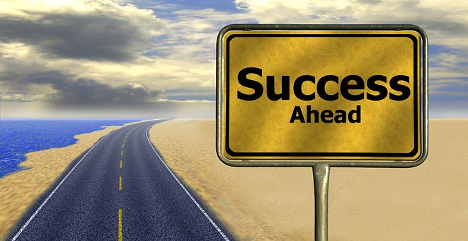 success ahead signage next to highway