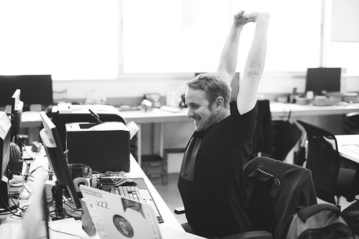 happy worker stretching and smiling at computer