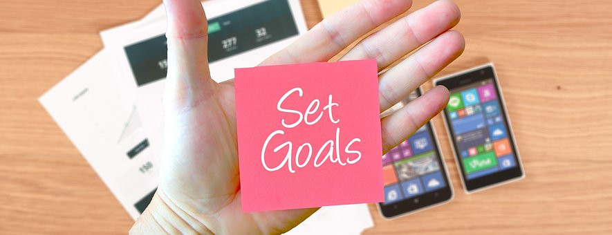 set goals, hand holding sticky note