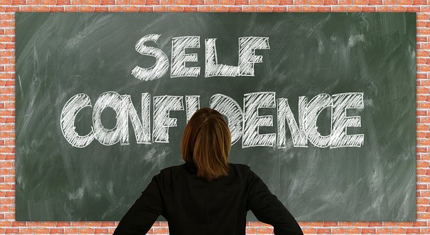 woman looks at self confidence written on board