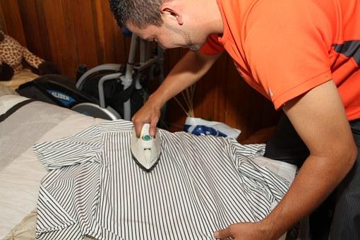 man ironing wrinkled shirt