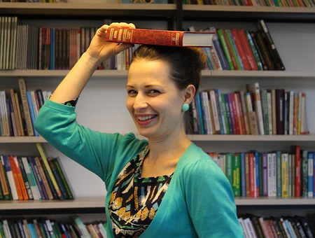laughter - woman smiling with book on her head