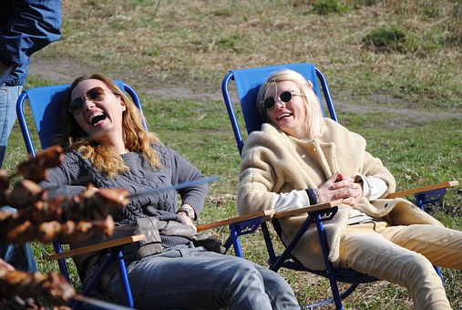 2 women in lawn chairs laughing - smiling