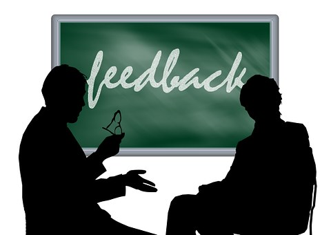 feedback written on chalkboard - 2 professionals talking