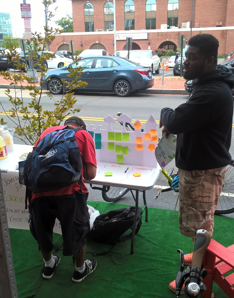 pop-up park visitor designs his corridorscape, noting an improvement for the anacostia river at park(ing) day 2018 on mlk. malusi kitchen, apacc coordinator, right. photo: michael bochynski.