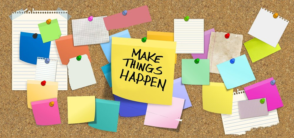 """bulletin board with sign saying """"make things happen"""", sticky notes, and pieces of paper."""